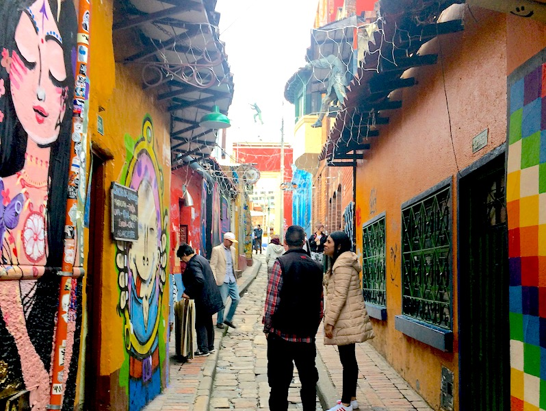 A couple walking down a narrow, colourful alleyway in Bogota, Colombia.