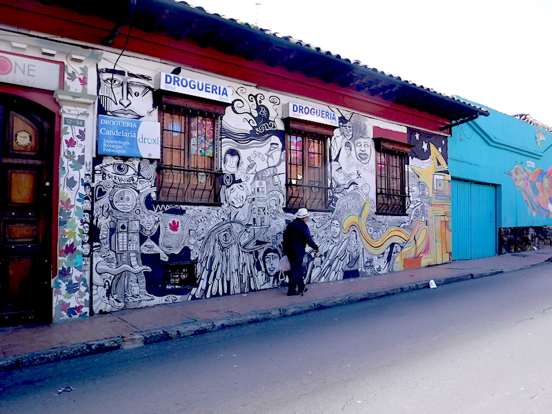 Old man walking past a graffiti decorated pharmacy in Candelaria district in Bogota, Colombia.