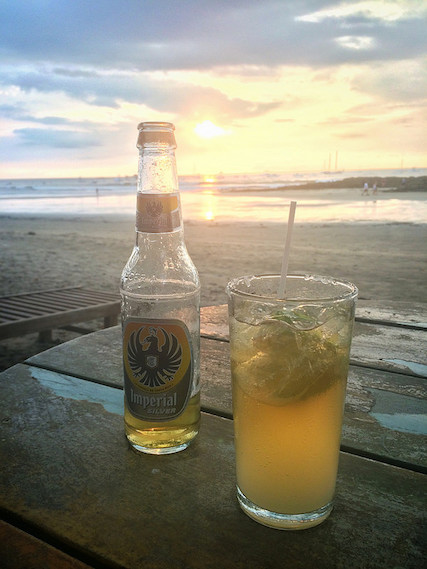 Beer and glass of lime, a chelada, on the beach at sunset in Tamarindo, Costa Rica