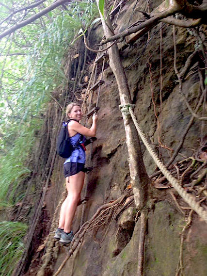 Woman climbing down a root covered cliff using a rope ladder.