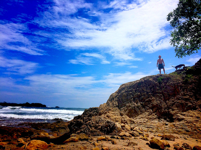 Man and a dog standing on top of a rocky cliff at a beach in Nosara, Costa Rica