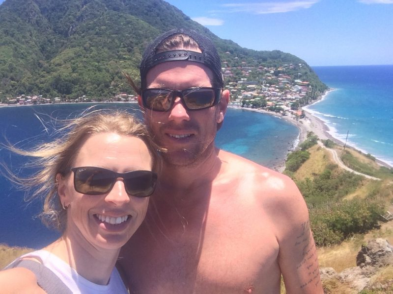 Couple selfie with green hills and turquoise waters of Dominica behind.