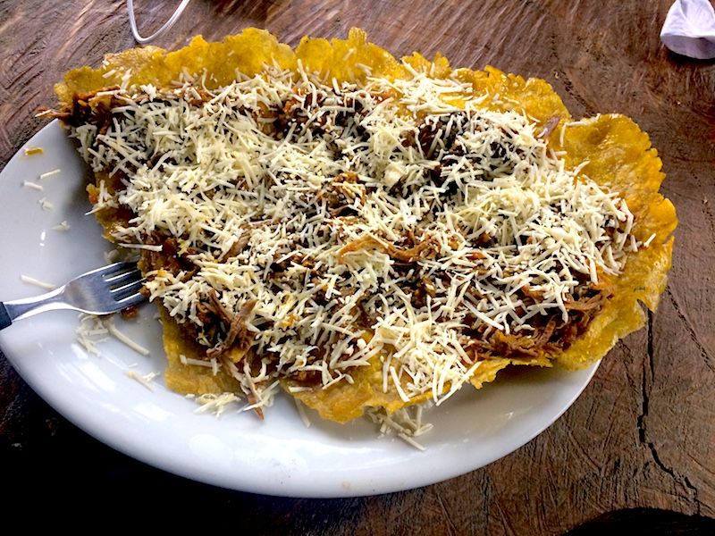 Plate covered in a patacon with meat and cheese.