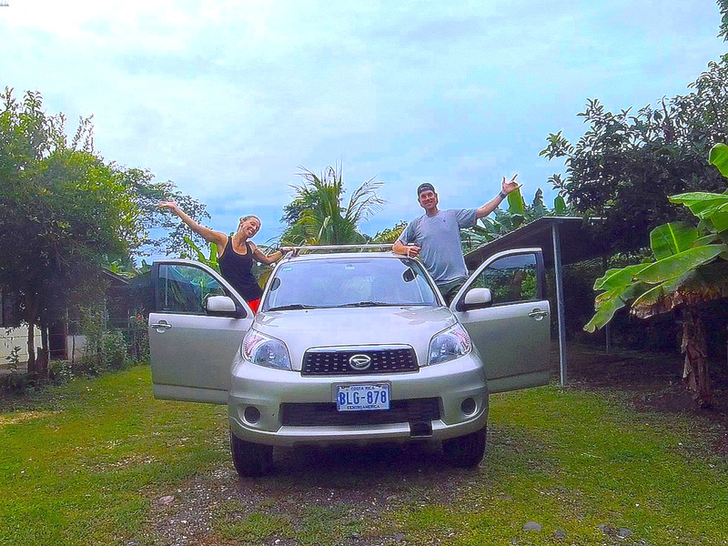 Couple hanging out doors of a rental SUV in Jicaral, Costa Rica.