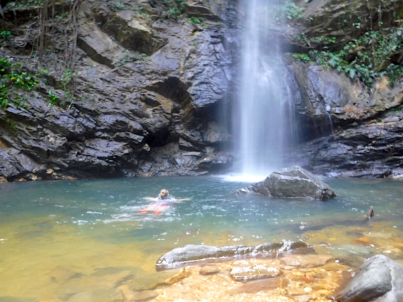 Girl swimming up to the bottom of Avocat Waterfall, Trinidad