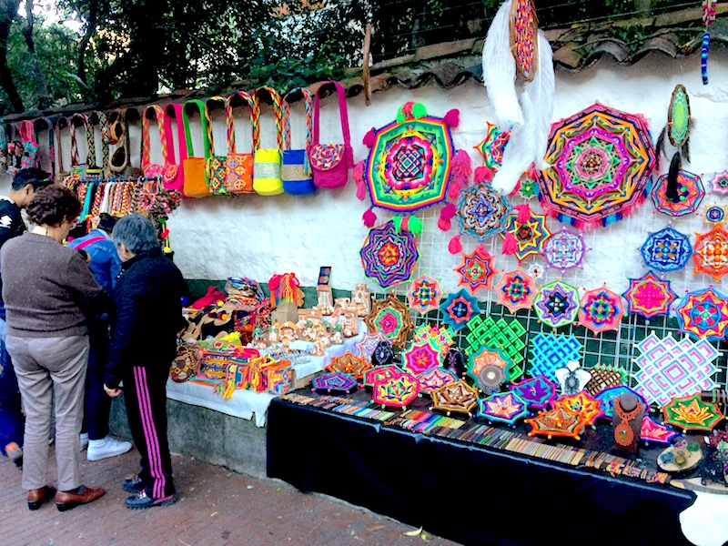 Colourful crafts hanging on a white wall in a street market in Usaquen, Bogota, Colombia