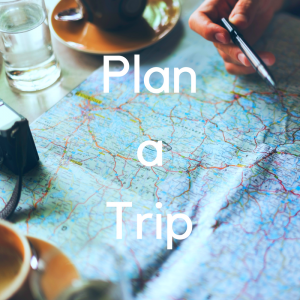 "A map on a table with a coffee and a pen. Text reads ""plan a trip""."