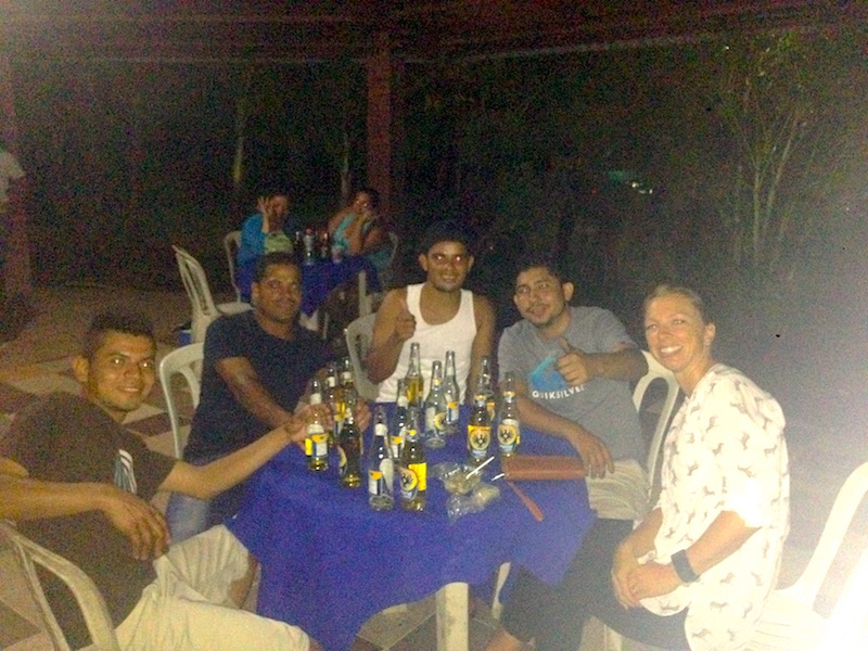 A group of people sitting around a table covered in beer bottles in Jicaral, Costa Rica.