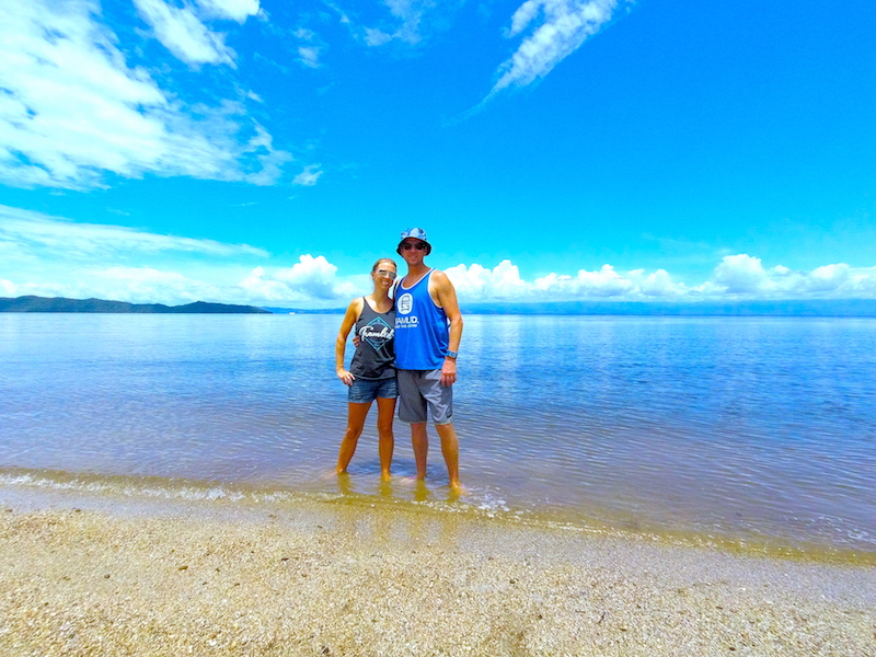 Couple standing in shallow water in a calm, blue beach on Costa Rica's Nicoya Peninsula.