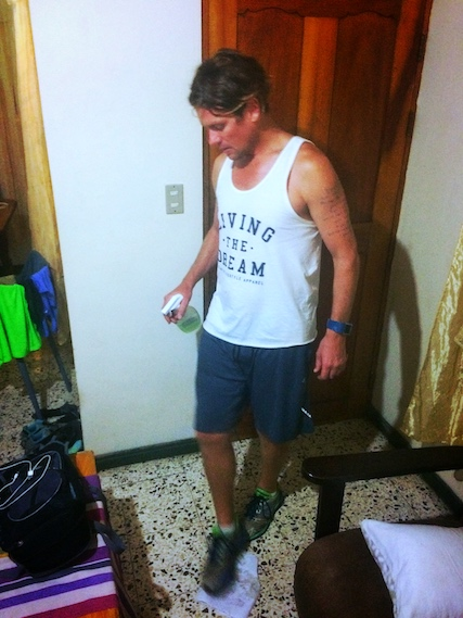 Man using his foot to clean the floor while dog sitting in Costa Rica.