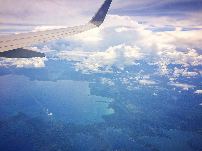 View of islands and water through the clouds with wing of a plane in view.