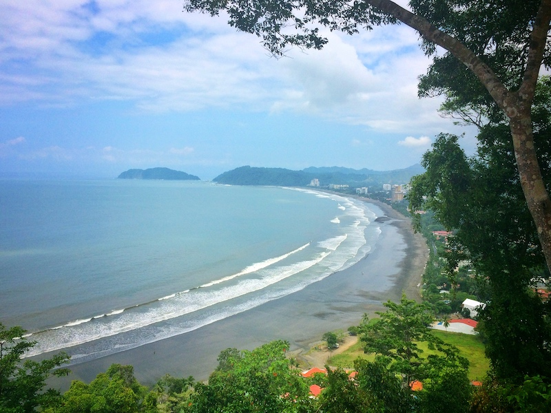 View from lookout of long sweeping bay with dark sand bordered by jungle in Jaco, Costa Rica