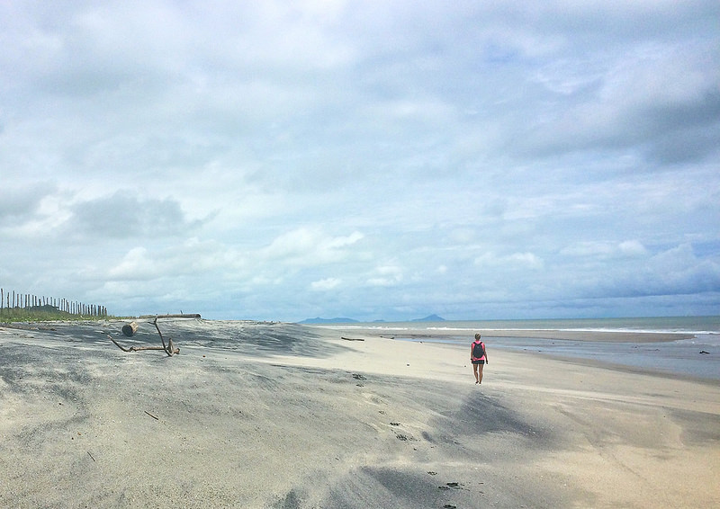 Woman walking along a long, wide sandy beach in Nueva Gorgona, Panama.