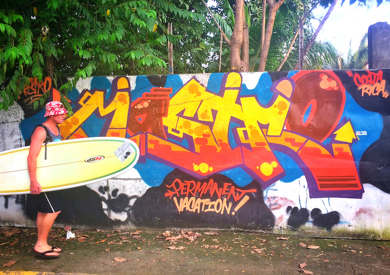 Man walking down street with surfboard in front of a wall covered in graffiti in Jaco, Costa Rica.