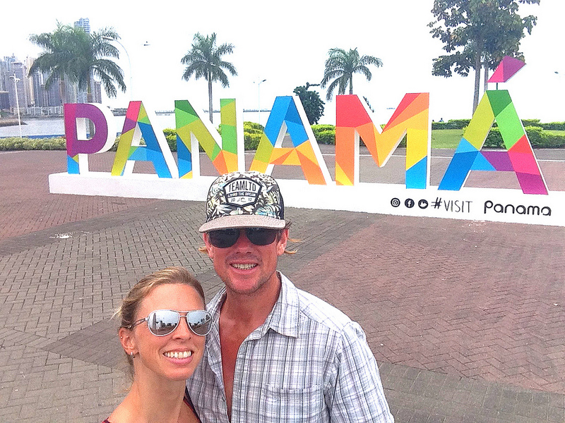 Couple standing in front of bright coloured Panama sign in Panama City.