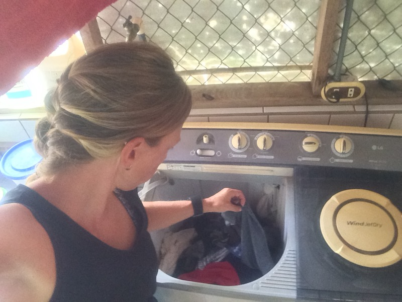 woman using an old-fashioned washing machine to do laundry.