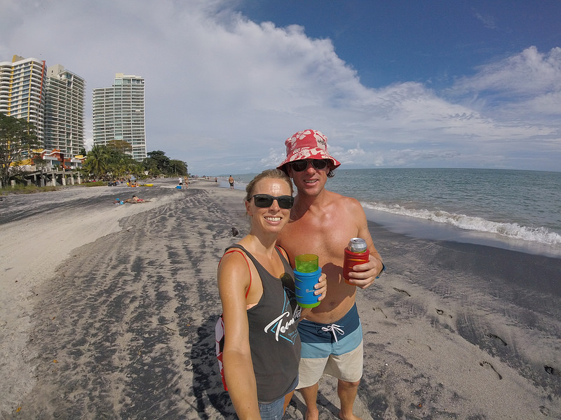 Couple having a drink on a sun-drenched black and white sand beach in Nueva Gorgona, Panama.