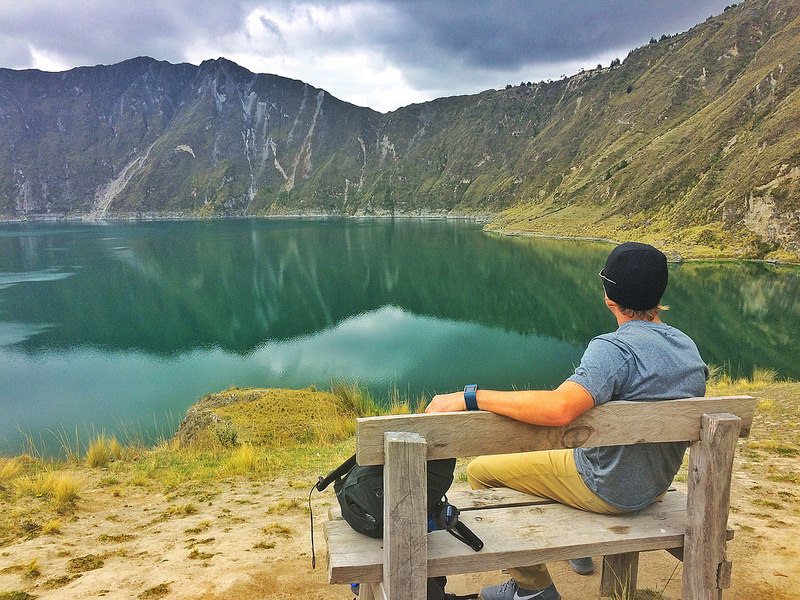 Man sitting on a bench looking at the emerald crater lake, Laguna Quilotoa, surrounded by mountains in Ecuador.
