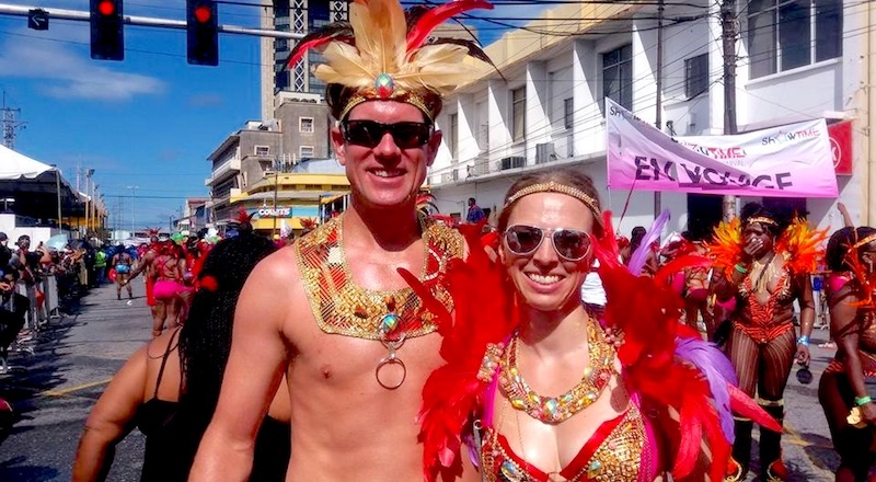 Man and woman in Trinidad Carnival costume with beads and feathers in the parade through Port of Spain.