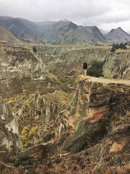 Man standing on the edge of a deep canyon in the Andes Mountains, Ecuador.