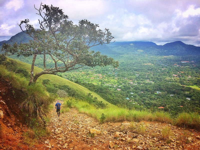 Man walking down a hiking trail with a great view across a valley to the right in El Valle, Panama.