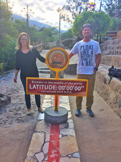 Couple straddling the red line that marks the equator near Quito, Ecuador.