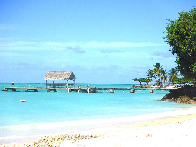 View of palapa roof on pier at Pigeon Point, Tobago with white sand and turquoise waters.