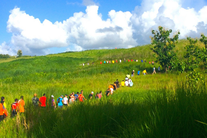 line of people walking through a field hashing, one of the best things to do in Trinidad