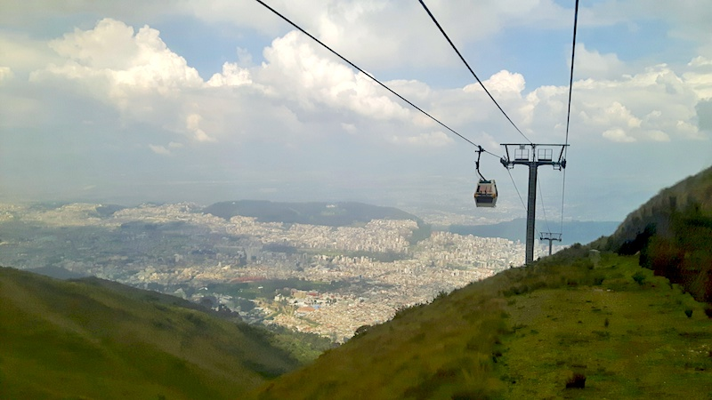 Cable car high in the air above the mountains and city views of Quito Ecuador.