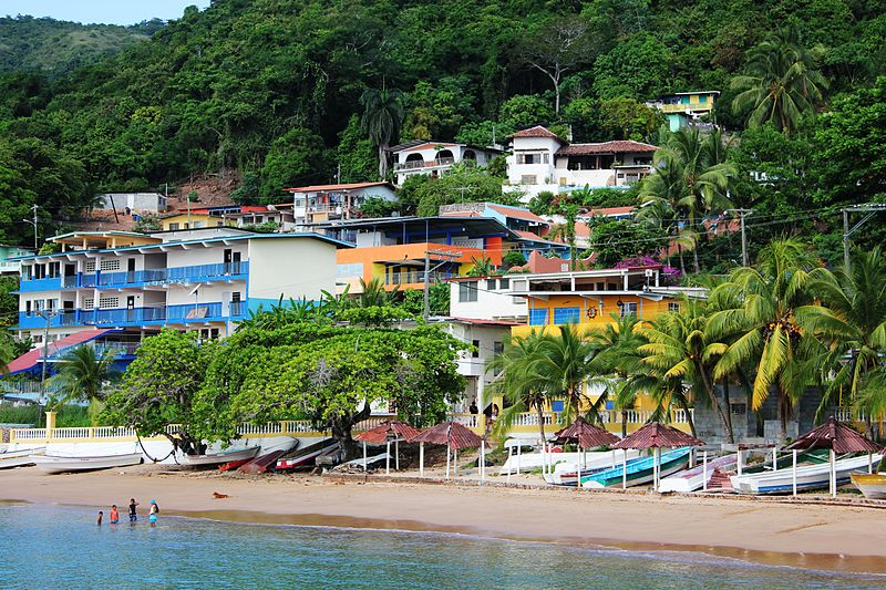 Colourful houses built into the lush hillside with fishing boats lining the beach on Taboga Island, Panama.