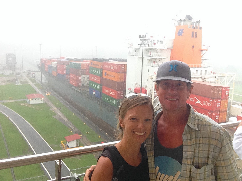 Couple smiling with a huge container ship behind passing through the Panama Canal, Panama.