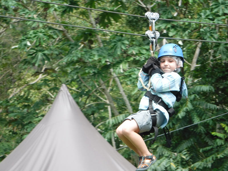 Young boy zip lining in jungle, Trinidad