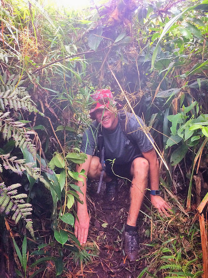 Man crouching through bushes on a hiking trail in El Valle, Panama.