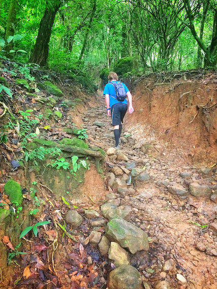 Man hiking up a steep dirt trail in El Valle de Anton, Panama.