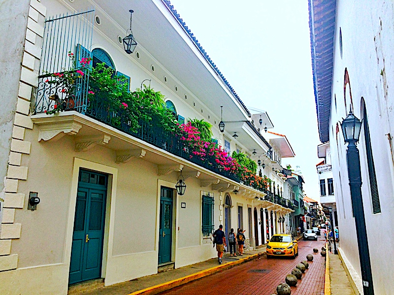 Colonial building with balcony covered in flowers on red cobblestone road in Casco Viejo, Panama City, Panama.