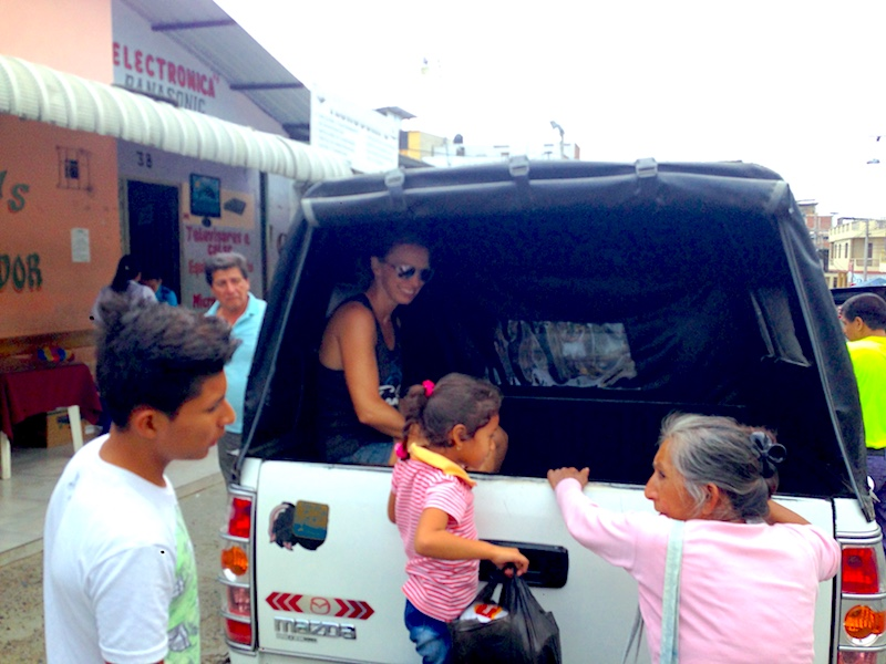 Elder lady and young girl climbing in the back of a pickup truck taxi to Santa Marianita, Ecuador