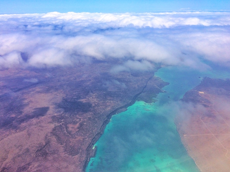 Galapagos Islands and bright turquoise waters through the clouds from a plane.