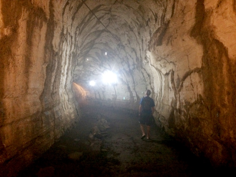 Man walking through a dark lava tube - a tunnel made from hardened lava rock on Santa Cruz island, Galapagos.