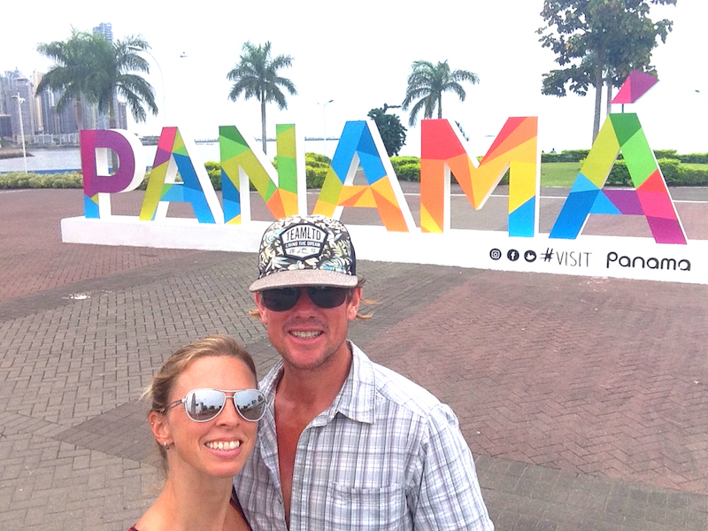 Couple standing in front of colourful Panama sign on Cinta Coster with palm trees in distance, Panama City.