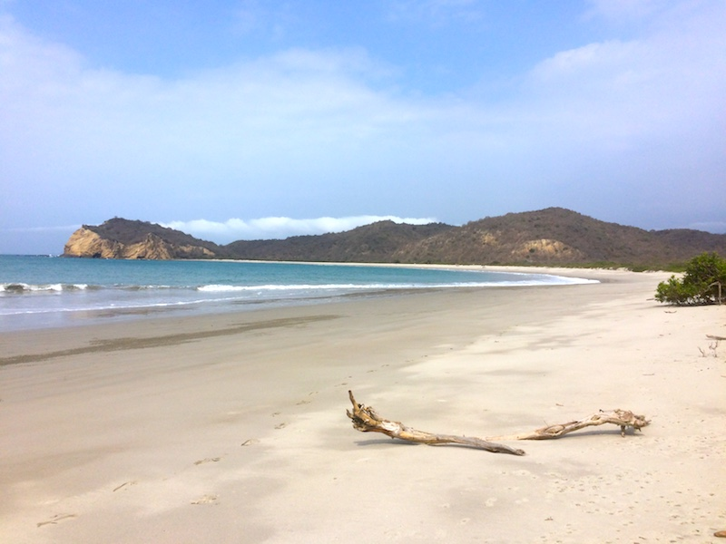 The wide sweeping bay with white sand and blue water of Playa los Frailes, Ecuador.