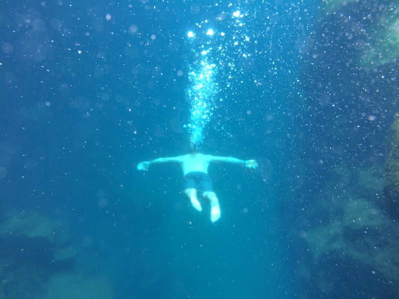 Man swimming through water with bubbles leading from him up to the surface at Las Grietas, Galapagos Islands.
