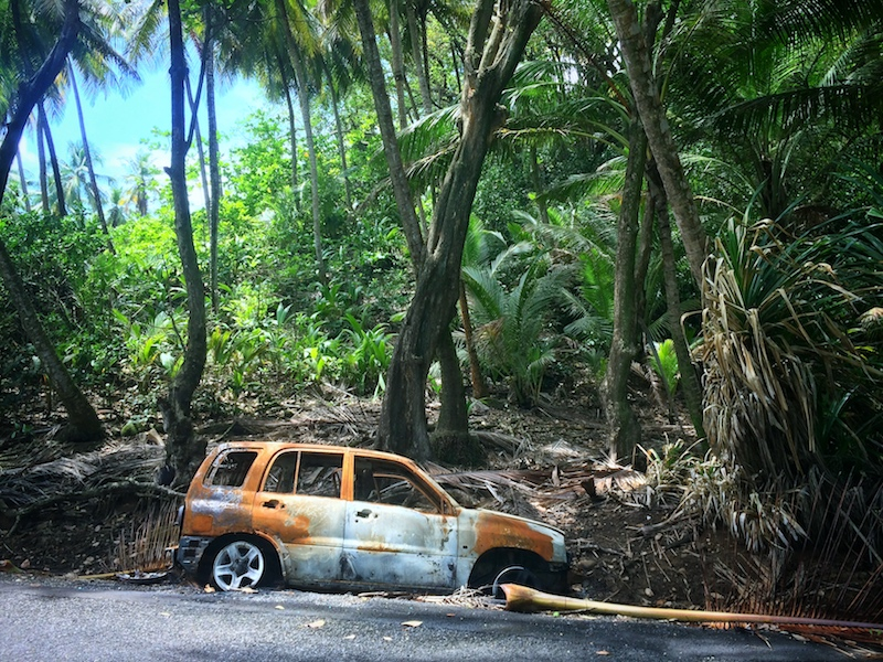 Rusted shell of a car on the side of the road surrounded by jungle in Dominica.
