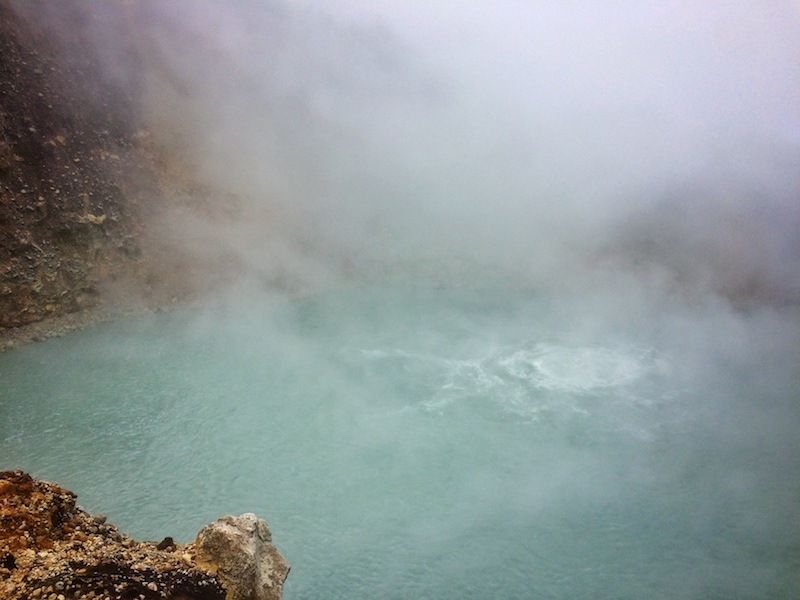 A blue water bubbling and obscured by steam in Dominica.