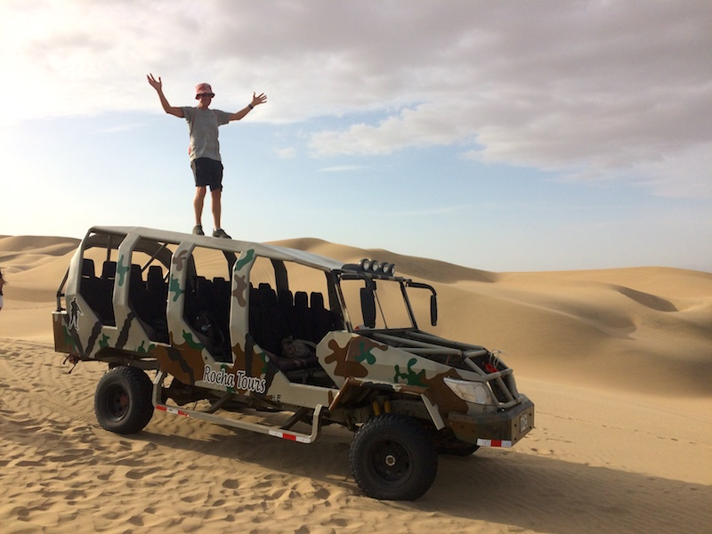 Man standing on top of a dune buggy in camouflage paint in the desert.