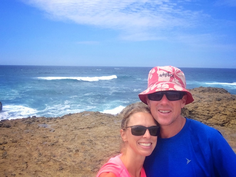 Couple standing on a rocky outcrop with rough Pacific Ocean behind at La Chocolatera, Ecuador