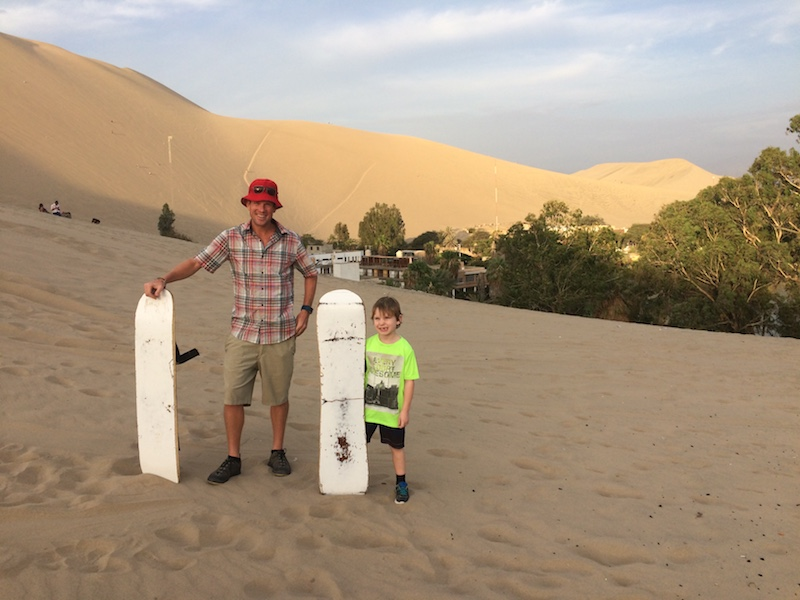 Man and boy standing in sand dunes holding sandboards in Huacachina, Peru.