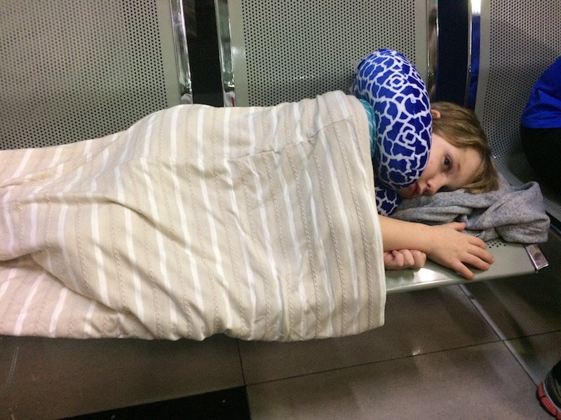 Boy laying on a bench with a scarf and head pillow to sleep.