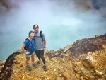 Couple standing on the edge of a boiling lake in Dominica.