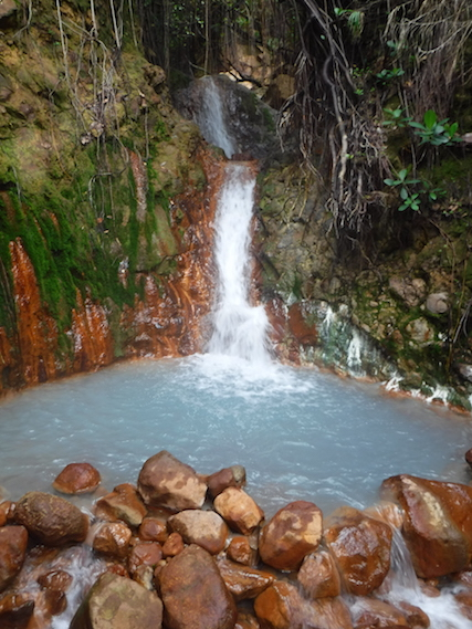 Milky, blue water at the bottom of a small sulphur hot spring waterfall on Boiling Lake hike, Dominica.
