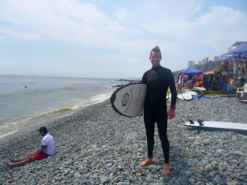 Man in wetsuit holding surfboard ready to go into the water at Miraflores beach in Lima, Peru.